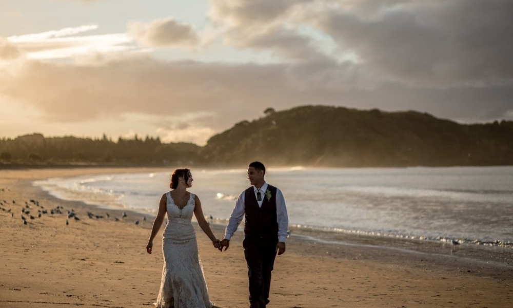 Newly Wed Couple enjoying a walk on the beach during sunset