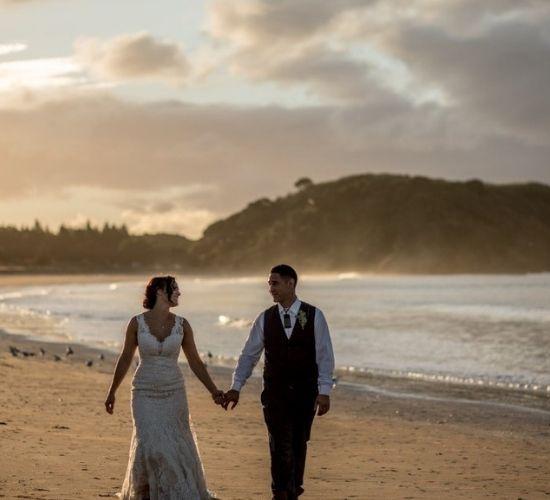 Bride and Groom walking down the beach at Taipa